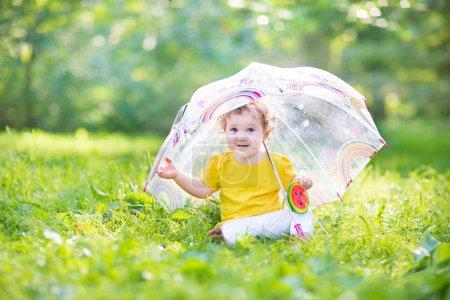 Baby girl under a colorful umbrella