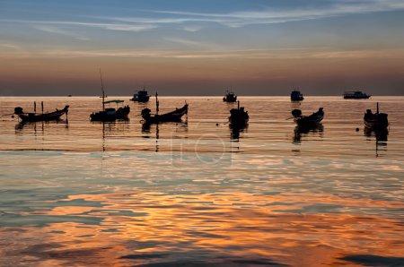 Longtail boats on seashore at sunset, Thailand