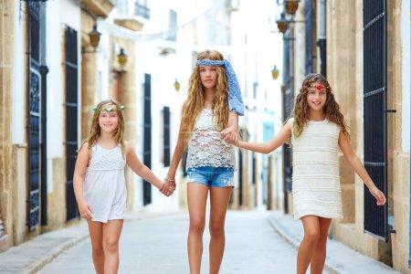 Kid girls walking hand in hand Mediterranean town