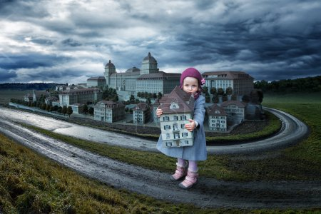 Little girl holding toy house