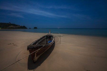 Abandoned wooden fishing boat on a sand beach at night